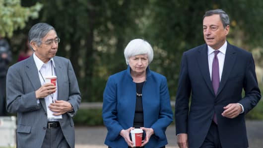 Haruhiko Kuroda, governor of Bank of Japan, from left, Janet Yellen, chair of Board of Governors of the Federal Reserve System, and Mario Draghi, president of the European Central Bank, walk the grounds at the Jackson Hole economic symposium, sponsored by the Federal Reserve Bank of Kansas City, in Moran, Wyoming, U.S., on Friday, Aug. 25, 2017.