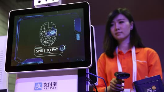 An Alibaba employee demonstrates 'Smile to Pay', an automatic payment system that authorize payment via facial recognition