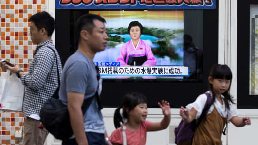 Pedestrians walk past a monitor showing a news program reporting on North Korea's 6th nuclear test on September 3, 2017 in Tokyo, Japan.