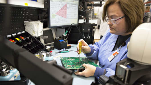 A worker attaches a component to a circuit board used in a liquid crystal display (LCD) screen for Boeing Co. aircraft at the Rockwell Collins Inc. production facility in Manchester, Iowa.
