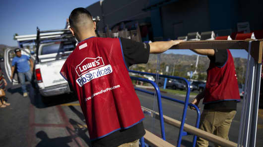 An employee loads a mirror onto a truck outside a Lowe's store in Burbank, California.
