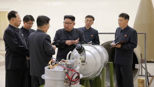 North Korean leader Kim Jong Un provides guidance with Ri Hong Sop (3rd L) and Hong Sung Mu (L) on a nuclear weapons program.