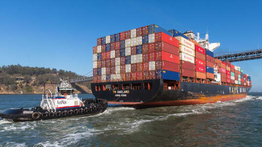 A cargo ship is guided into the Port of Oakland by a pair of tug boats.