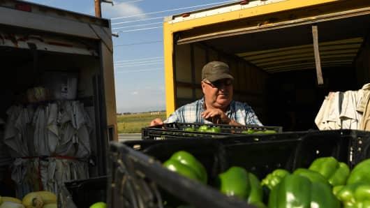 Joe Miller works loading produce at his farm on September 1, 2017 in Platteville, Colorado.