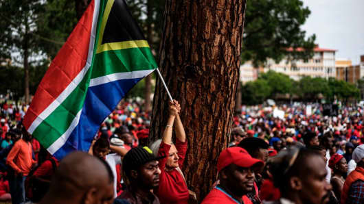 A woman waves the South African flag during a demonstration in Pretoria, calling for president Jacob Zuma to resign, in April 2017