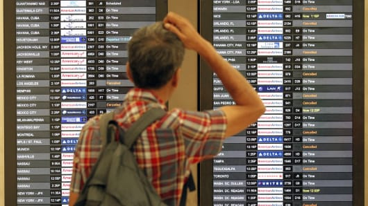 A passenger checks the departure board as flights at Miami International Airport are canceled
