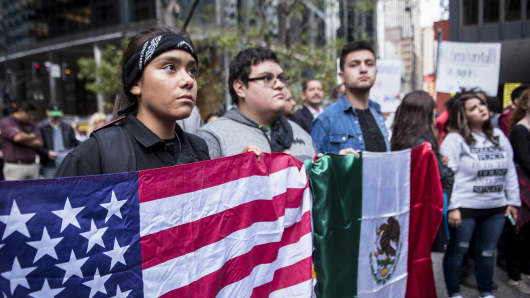 Demonstrators display American and Mexican flags while protesting the end of the Deferred Action for Childhood Arrivals (DACA) program in Chicago, Illinois, on Tuesday, Sept. 5, 2017.