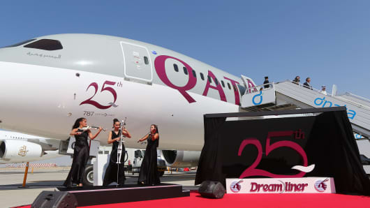 Musicians perform next to the 25th unit of Boeing 787 Dreamliner received by Qatar Airways and dislayed at the Dubai Airshow on November 9, 2015 in the Gulf Emirate.