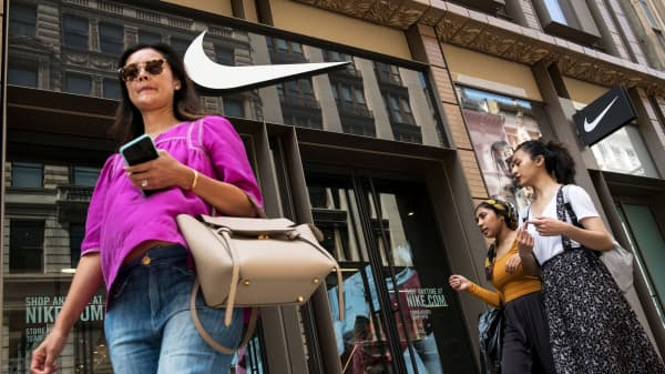 People walk past a Nike store in New York City.