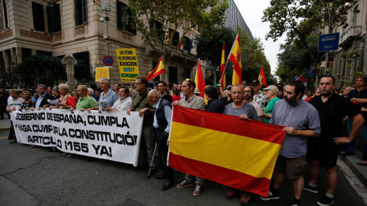 People hold Spanish flags and a banner reading 'Government of Spain, comply with and enforce the constitution: article 155 now' during a demonstration organised by the Spanish right-wing party Vox in front of the Spain Government Delegation in Barcelona, on September 6, 2017.