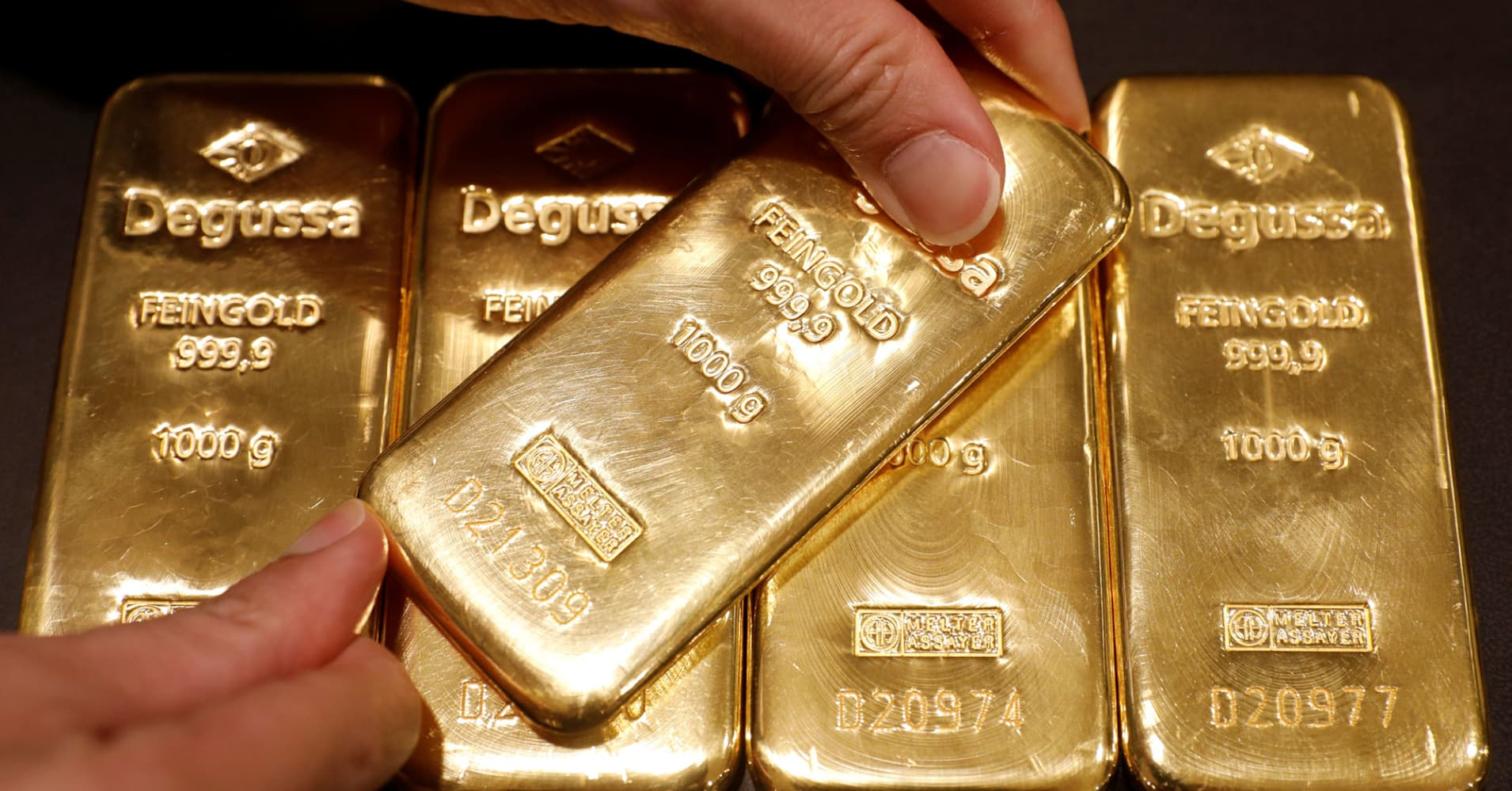Gold edges lower as dollar steadies, equities tick up
