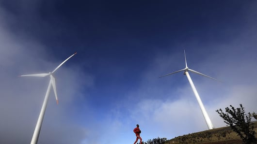 This photo taken on October 29, 2010 shows a man running past wind turbines in the early morning mist in the Ngong hills, some 25 kms south-west of Nairobi.