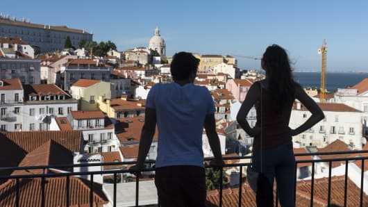 A couple look at Alfama, one of the city's historic neighborhoods, from the Miradouro de Santa Luzia in Lisbon, Portugal.