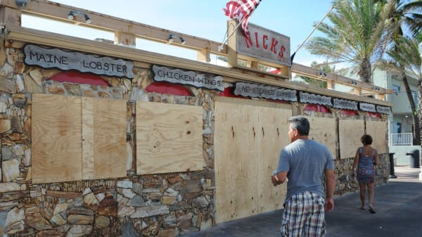 Tourists walk past a restaurant, closed in preparation for Hurricane Irma, in Fort Lauderdale, Florida on September 7, 2017.