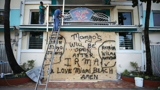 Workers board up the Mango's Restaurant and Night Club as the city prepares for the approaching Hurricane Irma on September 7, 2017 in Miami Beach, Florida.
