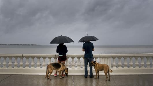 A couple walk their dogs on Bayshore Boulevard in Tampa, Florida, on September 10, 2017, where Tampa residents are fleeing the evacuation zones ahead of Hurricane Irma's landfall.