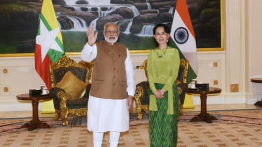 India's Prime Minister Narendra Modi waves as he poses for a photograph with Myanmar's State Counsellor Aung San Suu Kyi in Naypyidaw on September 6, 2017.