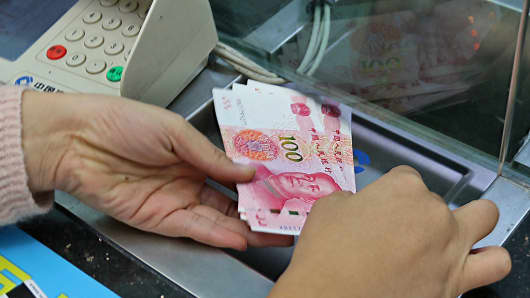 A citizen withdraws new 100 yuan notes at a bank on November 12, 2015 in China.