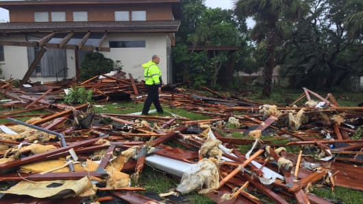 Palm Bay officer Dustin Terkoski walks over debris from a two-story home at Palm Point Subdivision in Brevard County after a tornado touched down on Sunday, Sept. 10, 2017.
