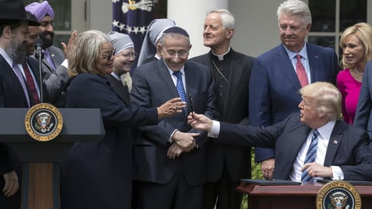 President Donald Trump is surrounded by religious leaders after signing an executive order in the Rose Garden in May 2017 that took aim at Obama-era regulations intended to protect gay people from discrimination and ensure that women have access to birth control.