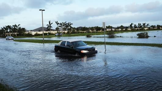 Cars make their away through a flooded street the morning after Hurricane Irma swept through the area on September 11, 2017 in Bonita Springs, Florida.
