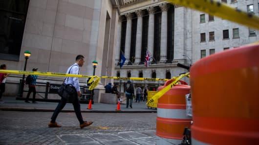 Pedestrians walk past the New York Stock Exchange.