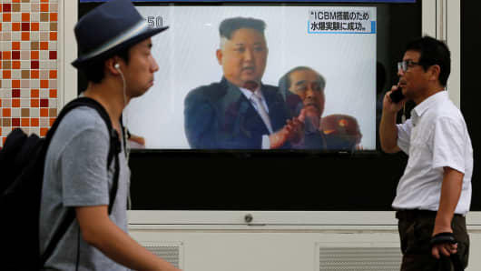 Men walk past a street monitor showing North Korea's leader Kim Jong-Un in a news report about North Korea's nuclear test, in Tokyo, Japan, September 3, 2017.