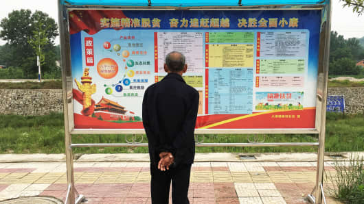 A man looks at a notice board in the settlement of Dajing in rural Shaanxi province, China.