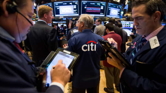 A trader, center, wears a Citigroup jacket while working on the floor of the New York Stock Exchange.