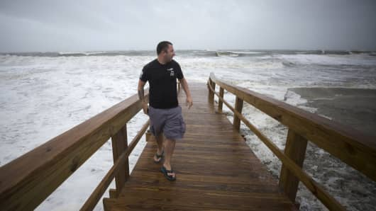 Mike Locklear looks at the beach erosion from a beach crossover caused by storm surge from Tropical Depression Irma, Monday, Sept., 11, 2017 on Tybee Island, Ga.