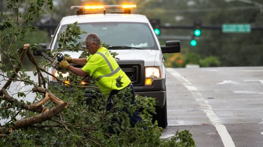 An emergency worker clears a fallen tree after Hurricane Irma made landfall in Downtown Tampa, Florida, September 11, 2017.