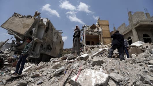 Yemeni men stand on the debris of a house, hit in an air strike on a residential district, in the capital Sanaa on August 26, 2017.
