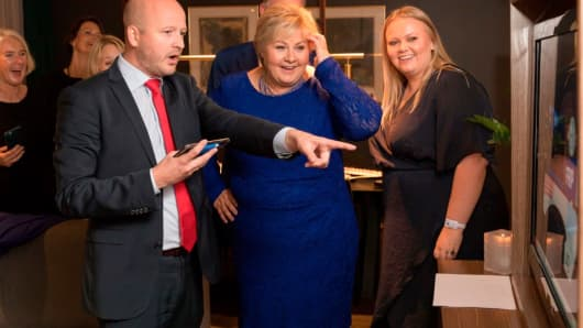Norway's Prime Minister Erna Solberg (centre, in blue) looks at a TV screen displaying the result of the general election