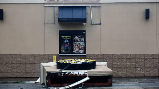A sign from a Hungry Howies restaurant sits on the ground in front of the drive through window after high winds caused by Hurricane Irma impacted the area on September 11, 2017 in Fort Meade, Florida.