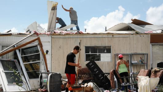 Olga Teakell, on right, and her family clean her mobile home after it was damaged by Hurricane Irma in Naples, Florida, September 11, 2017.