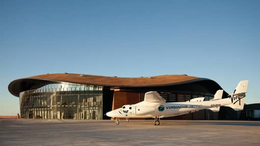 Virgin Galactic's SpaceShipTwo and mothership WhiteKnightTwo stand before their new home, VG Gateway to Space at Spaceport America.