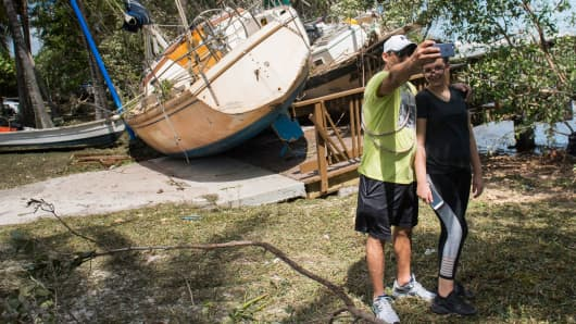 People pose for a selfie as a boat sits onshore in a park after being beached by storm surge from Hurricane Irma in Coconut Grove, Florida, September 11, 2017.