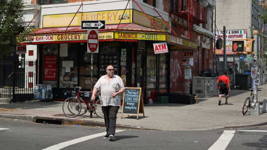 Pedestrians pass a bodega on Metropolitan Avenue in Williamsburg, Brooklyn, New York.