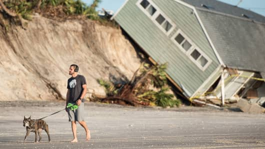 Jose Orosz walks his dog Karen by a beachfront home destroyed by Hurricane Irma on September 13, 2017 in Vilano Beach, Florida.