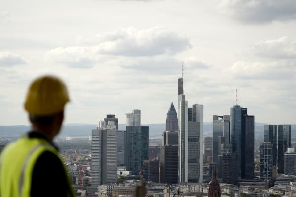 Wearing a hard hat a man looks out over the city skyline in Frankfurt/M., western Germany, on September 20, 2012