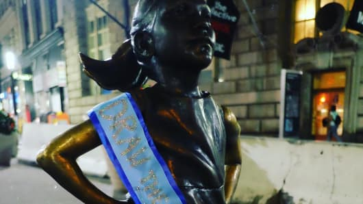 "The ""Fearless Girl"" sculpture was draped with a blue ribbon that read ""Draw a Blue Line"" on Sept. 14th, 2017."