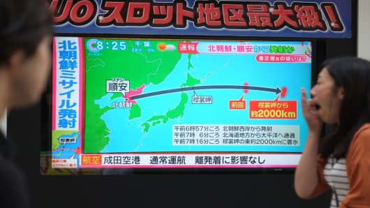Pedestrian look at a television screen broadcasting a news report in Tokyo on September 15, 2017, following a North Korean missile test that passed over Japan.