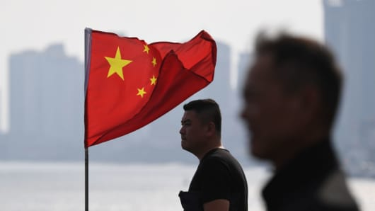 Two Chinese men stand near a Chinese flag as they look out towards North Korea while visiting the Broken Bridge, in the Chinese border city of Dandong, in China's northeast Liaoning province on September 5, 2017.