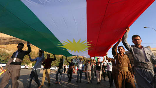 Iraqi Kurds holds a large Kurdish flag as they walk near the citadel towards a gathering urging people to vote in the upcoming independence referendum in Arbil, the capital of the autonomous Kurdish region of northern Iraq, on September 13, 2017.