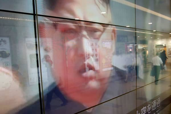 Passersby are reflected in a TV screen reporting news about North Korea's leader Kim Jong Un and their missile launch, in Tokyo, Japan, September 15, 2017.