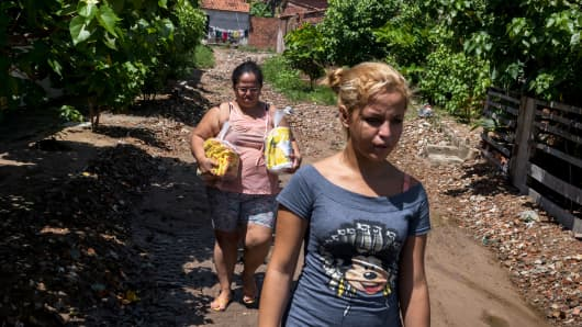Celene da Silva, one of thousands of door-to-door vendors for Nestlé, and her daughter Sabrina make deliveries in Fortaleza, Brazil, May 20, 2017.