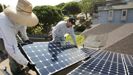 Workers install solar panels on a residential home in Santa Monica, Calif.