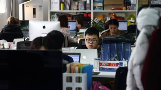 Workers at their desks inside Tech Temple, a co-working space for start-ups sponsored by Infinity Ventures Partners in Beijing, China, on March 12, 2015.