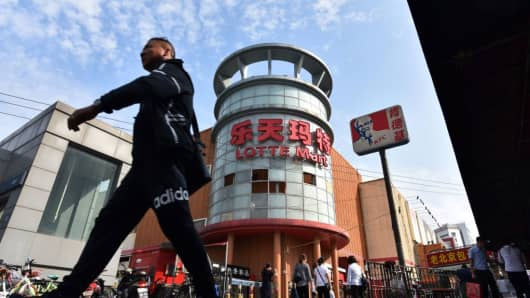 A man walks near a closed Lotte store in Beijing on September 15, 2017.