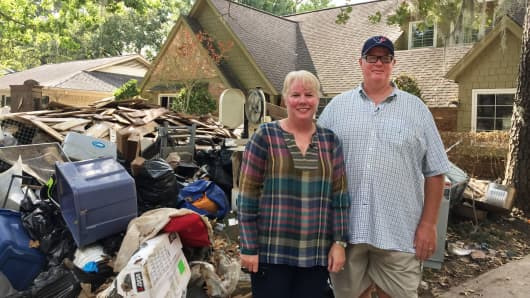Jennifer and Andy Taylor stand in front of the remnants of their Houston home.